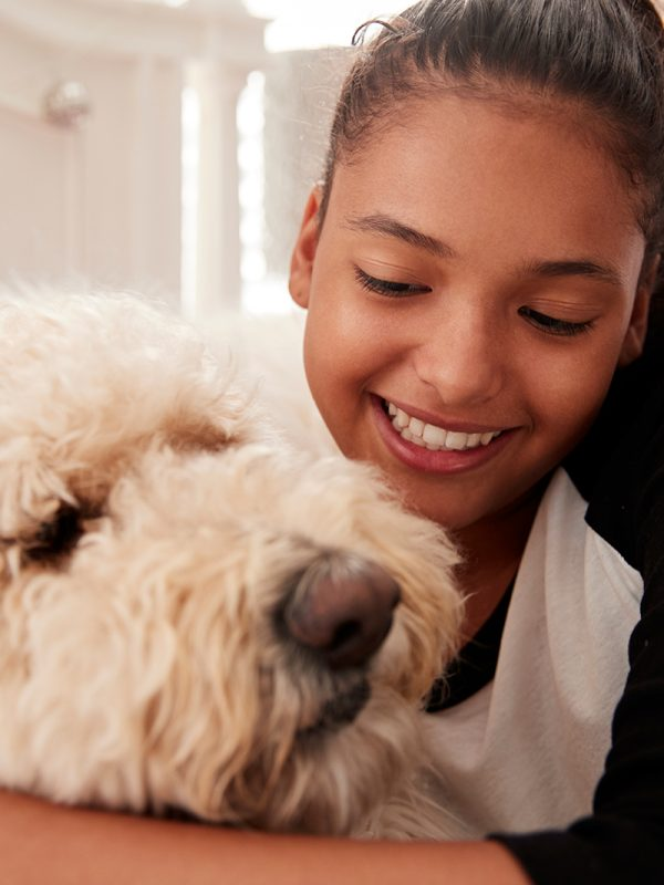 young-teen-girl-embracing-pet-dog-on-her-bed-PGQHKBW.jpg